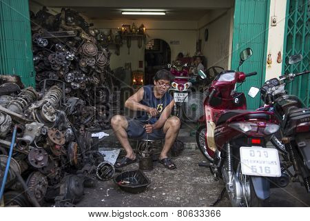 BANGKOK, THAILAND - DECEMBER 25, 2014: Street Photography of owner of a small body shop repairs scooter.