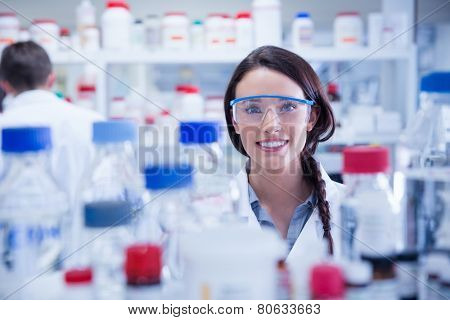 Portrait of a smiling chemist wearing safety glasses in lab