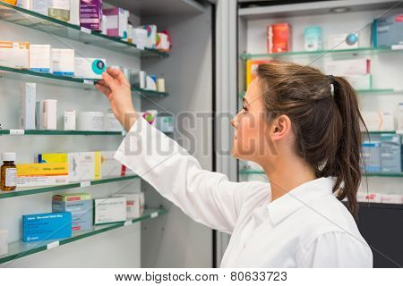 Junior pharmacist taking medicine from shelf at the hospital pharmacy