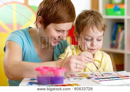 mom and kid boy paint together at home