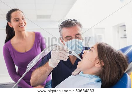 Pediatric dentist examining young patient with a suction tube in dental clinic