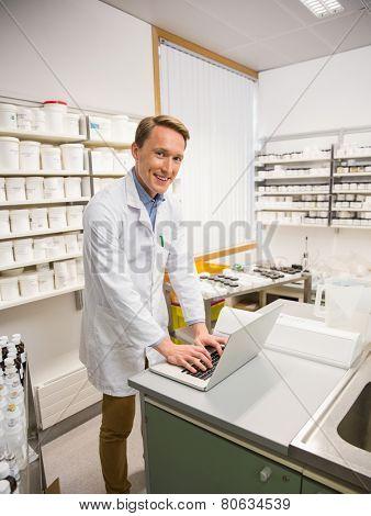 Happy pharmacist using his laptop at the hospital pharmacy