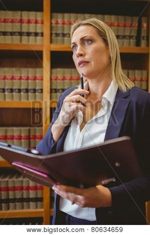 Thinking female librarian holding textbook in library