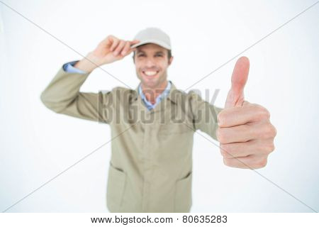 Portrait of smiling delivery man wearing cap while gesturing thumbs up over white background