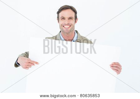 Portrait of happy delivery man pointing at blank billboard against white background