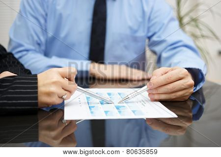 Businessman And Businesswoman Are Analyzing Report With Full Of Graphs