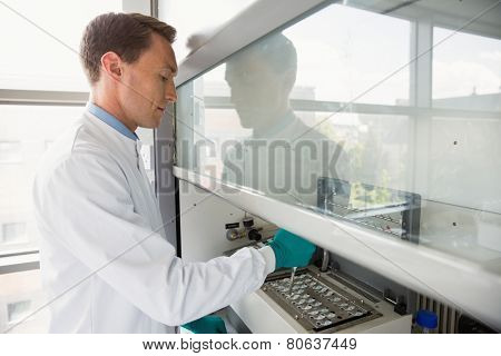 Young scientist using a pipette in chamber at the laboratory