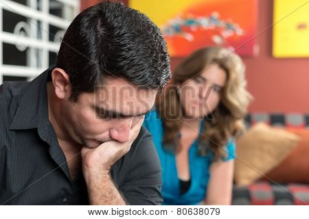 Divorce, marital problems- Sad and worried man with his wife looking at him