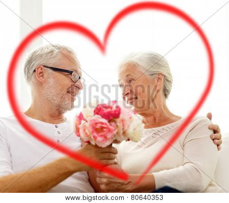 family, holidays, age and people concept - happy senior couple holding bunch of flowers at home with big red heart shape