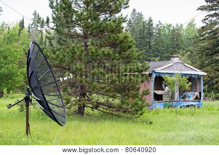 Satellite Dish In Front Of Abandoned House Or Shack