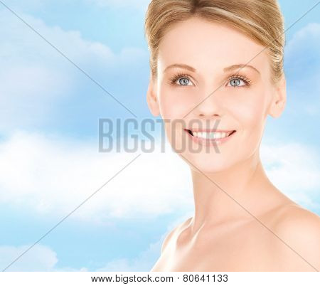 people, beauty and health care concept - close up of smiling young woman over blue sky background
