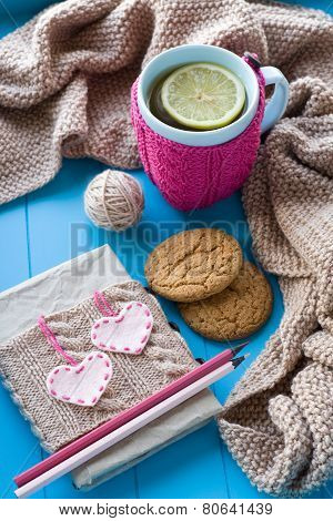 A Cup Of Tea In Sweater With Lemon, Old Notebook With Hearts Of Felt, Beige Knitted Blanket