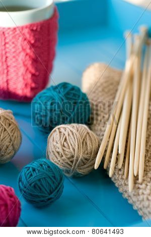 Bright Balls Of Yarn, Wooden Knitting Needles, Knitted Blanket Lying On A Blue Background
