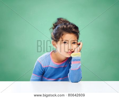 education, people, childhood and emotions concept - sad or bored little school girl over green chalk board background