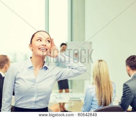 business, office and gossip concept - smiling businesswoman listening gossig at office