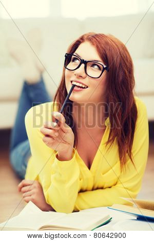education and home concept - smiling student girl in eyeglasses reading books at home