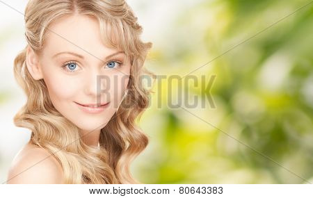 people, beauty, body and skin care concept - beautiful woman face and hands over green background