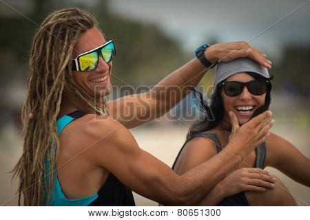 Laughing Happy Couple in Sunglasses having fun on the Beach.