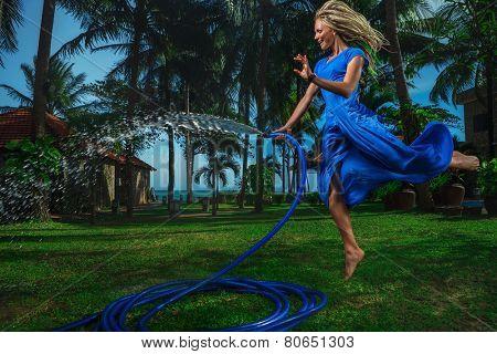 Beautiful woman having fun with garden hose splashing summer rain.