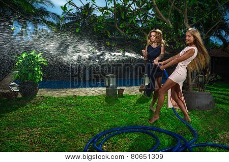 Beautiful women having fun with garden hose splashing summer rain.