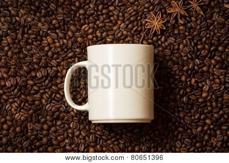 White Mug Against Coffee Beans With Anise Stars Lying Like Steam