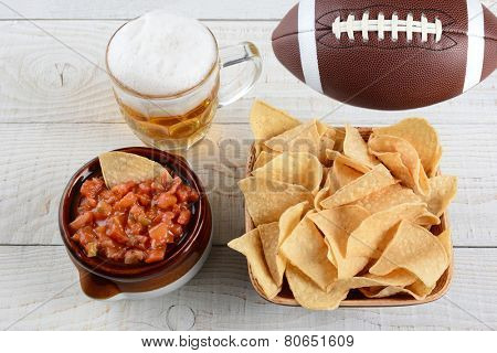 High angle shot of a bowl of corn chips a crock full of fresh salsa a mug of beer and an American football on a whitewashed rustic wood table. Horizontal format.