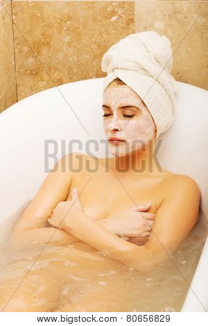 Woman relaxing in bath with face mask, wearing towel on head.