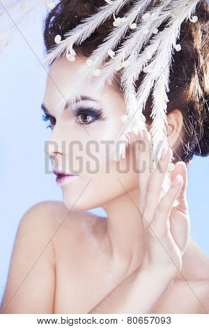 Beauty model with cold winter make up over blue background. Snow queen.