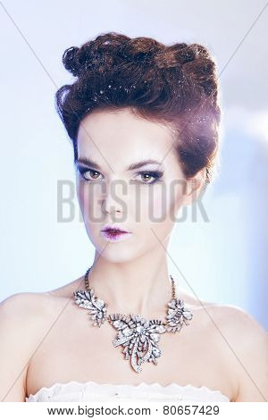 Beauty woman over blue background with luxury accessories. Winter beauty woman. Snow queen.