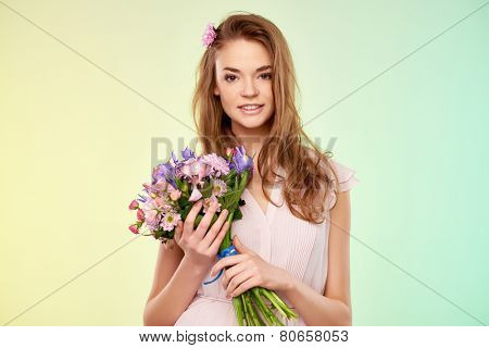 Beautiful young woman with bunch of flowers
