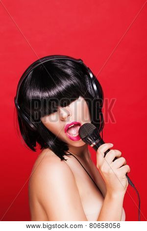 Woman listening to music on headphones enjoying a singing. Closeup portrait of beautiful girl with p
