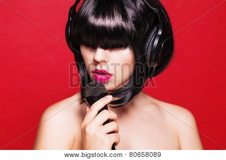 Closeup portrait of beautiful woman with microphone. Karaoke. on red background