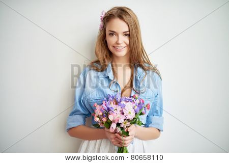 Charming girl in casualwear holding fresh bouquet