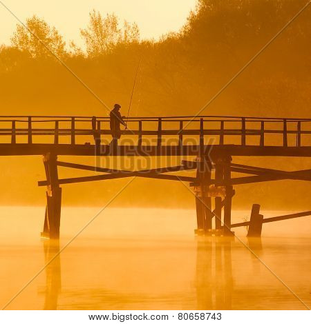 Beautiful sunset by the river. Fisherman on the bridge