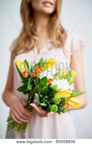 Young female holds bunch of fresh roses, tulips and chrysanthemums