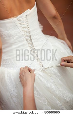 Bridesmaid Helping The Bride To Put Her Wedding Dress On. Tying Bow On Wedding Dress