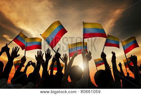 Group of People Waving Columbian Flags in Back Lit