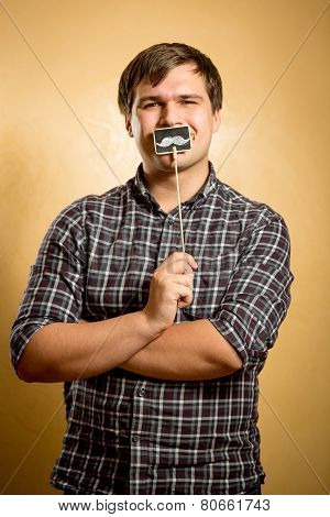 Funny Man Holding Fake Mustache On Stick At Mouth