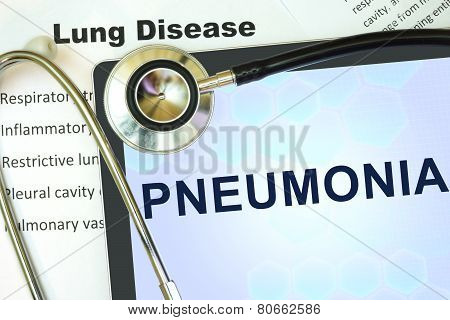 Tablet with word Pneumonia and stethoscope.
