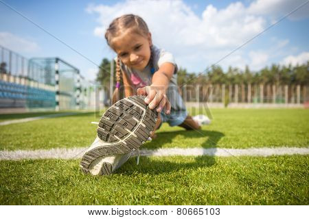 Young Girl Stretching On Grass Before Running