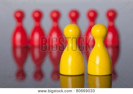 Two Yellow Figures In Front Of Many Red