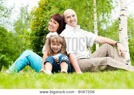 Family Of Three On Grass
