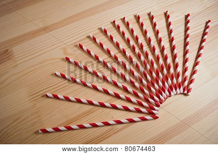 Striped straws on wooden background