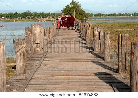 Monks  And Visitors Walking On The U-Bein Bridge.