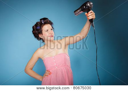 Girl With Curlers In Hair Holds Hairdryer