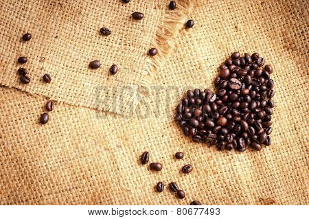 Heart With Roasted Coffee Beans On The Burlap Background