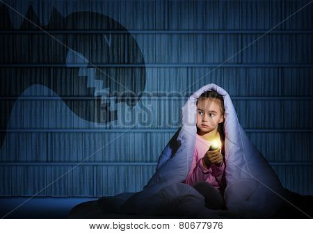 girl under the covers with a flashlight