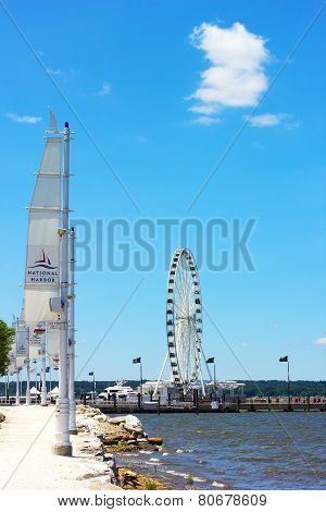 Pathway along the Potomac River waterfront and a pier with Ferris under blue summer sky.