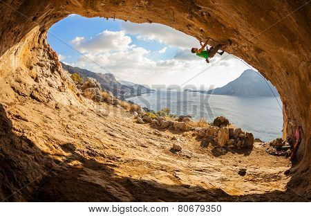 Young man lead climbing in cave
