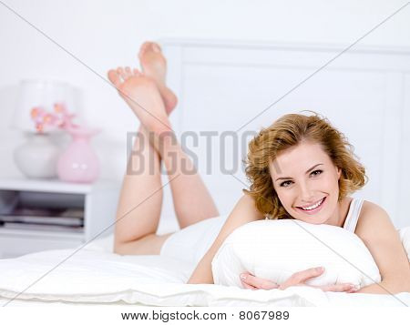 Woman With Happy Smile Lying On A Bed At Home